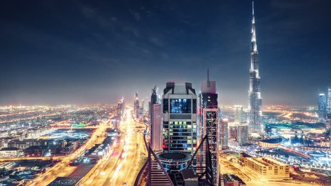 Fantastic nighttime skyline of a big modern city. Scenic aerial view of Dubai downtown skyscrapers and highways with light trails. 4K time lapse. Colouful travel background.
