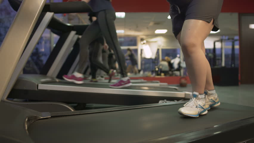 Unhealthy fat woman barely walking on treadmill, working hard to lose weight