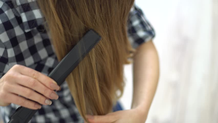 Woman doing hairstyle with hair straightener | Shutterstock HD Video #24908396
