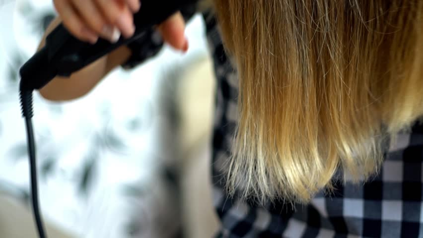 Woman doing hairstyle with hair straightener, isolated on white in super slow motion   Shutterstock HD Video #24908426