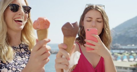 Young women taking photo of ice cream on beach Girl photographing Italian Gelato outdoors in summer sunshine Girls enjoying European vacation travel adventure Amalfi Coast Italy