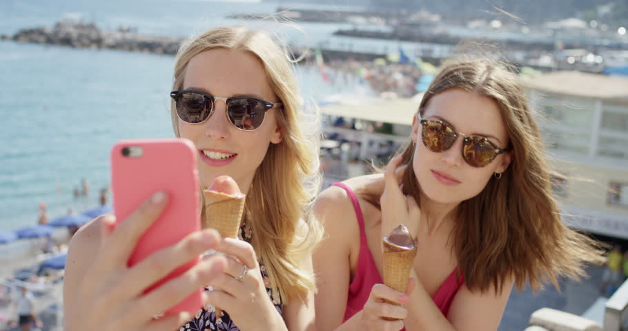 Young women eating ice cream on beach Best friends licking Italian Gelato outdoors in summer sunshine Girls enjoying European vacation travel adventure Amalfi Coast Italy