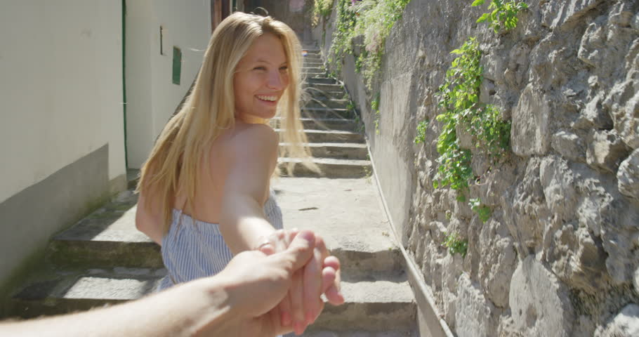 Young couple holding hands woman leading boyfriend up steps through street in Italian town POV travel concept Amalfi Coast Positano Italy