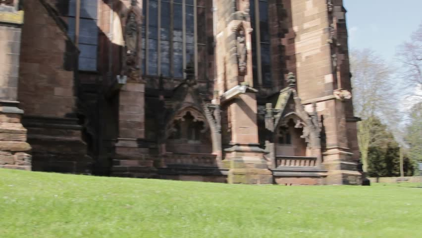 Panning Shot showing Lichfield cathedral in all its Gothic Grandeur from foundations to spire, weatherworn stone, standing firm against a blue sky and lush green grass in the small city of Lichfield.