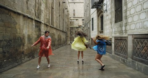 Diverse group of friends dancing freestyle in European City wearing multi colored poncho rain coats in rainy weather celebrating travel adventure
