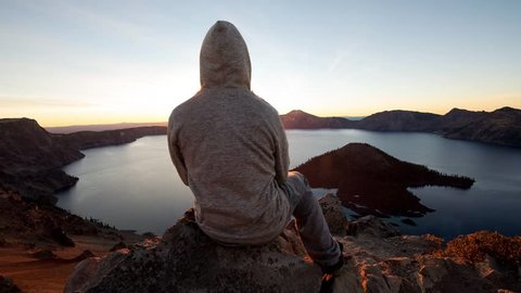 2.5D parallax video hooded man sitting on edge of rock cliff watching sunrise above crater lake, Oregon, USA
