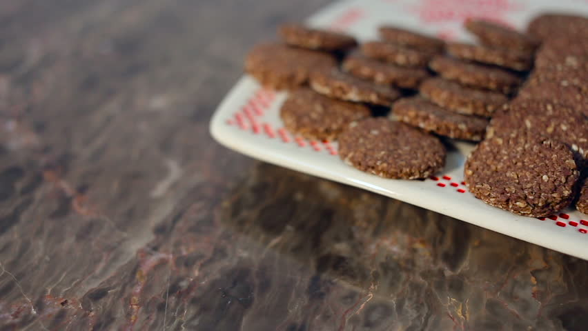 Close up Dolly shot of Homemade Oatmeal cookies with sesame seeds on a white plate with ornament. #24966872
