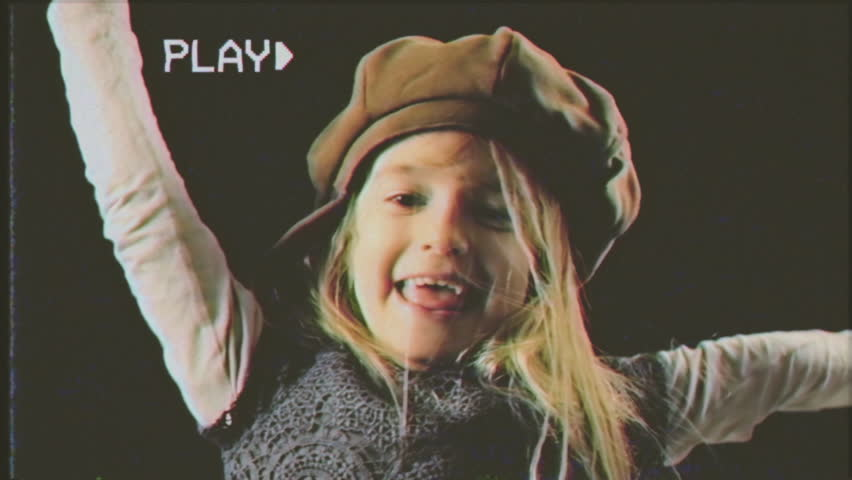 Fake VHS tape: a cute little girl making funny faces. Close-up studio shot, black background.