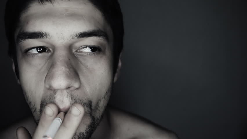 Young man smoking a cigarette looking at camera