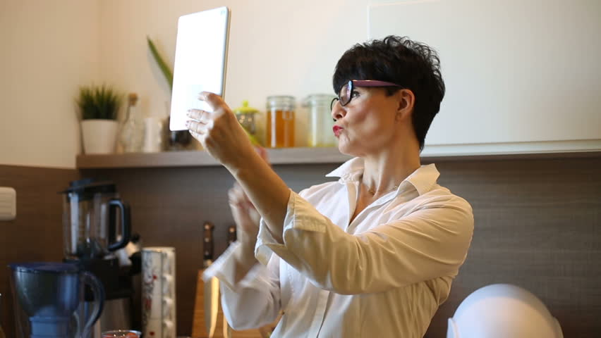 Attractive businesswoman standing in the kitchen and doing selfies on tablet  | Shutterstock HD Video #25006376
