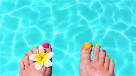 Seamless loop - Woman bare feet with frangipani flower, turquoise water in the background, video HD