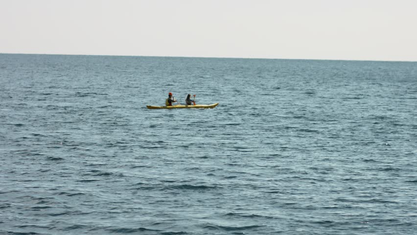 People having fun rowing at sea at kayaks