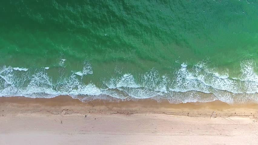 Tropical beach video loop showing seamless never ending footage with aerial bird eye view of green foaming ocean waves crushing against the coast line of Florida and overhead view of a seldom tourist | Shutterstock HD Video #25022873