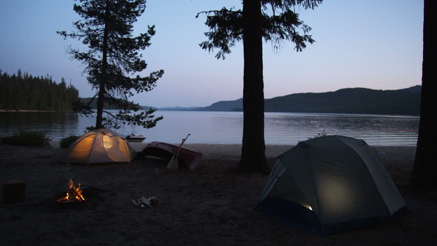 Two tents at a scenic lakeside campsite at dusk. Cheery campfire burns in a fire ring.