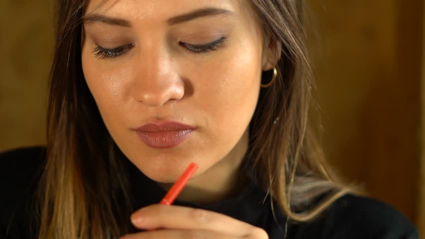 Young Caucasian woman enjoying a drink with the straw. Drinking cola or soda pop with a straw. Close up portrait shot.