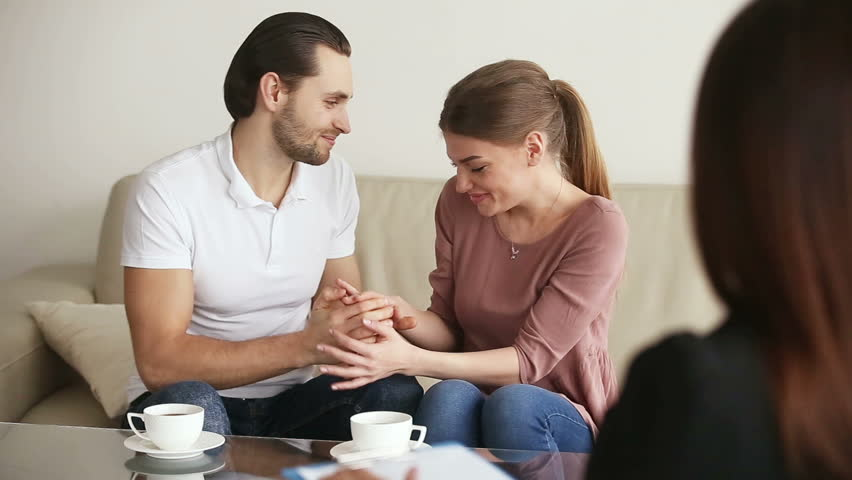 Family facing relationship difficulties. Young upset couple visiting professional psychotherapist office, listening to marriage counselor advice, looking at each other, making up after therapy session