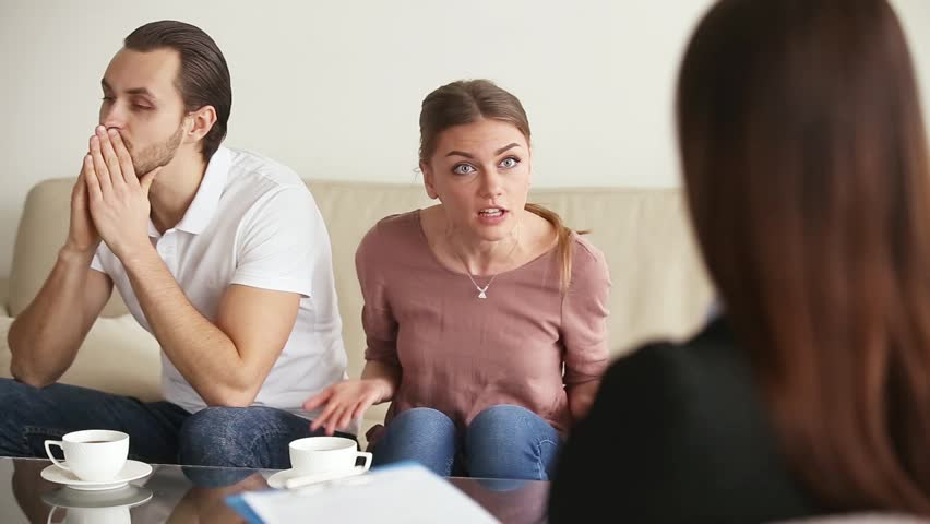 Family facing relationship difficulties. Young couple visiting professional marital therapist office, fighting with each other at therapy session. Woman yelling and complaining to marriage counselor