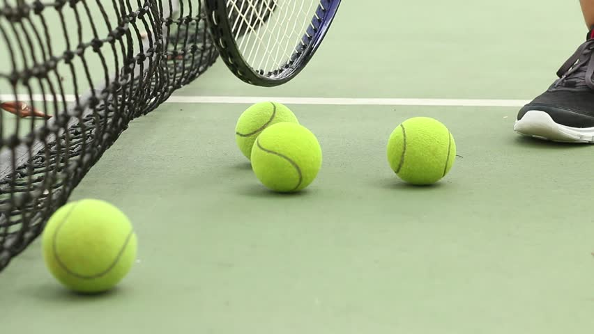 Rolling tennis ball on ground at green court with net #25085876