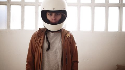 Cute motorcyclist blonde woman takes off her retro helmet and smirks happily in the bright room