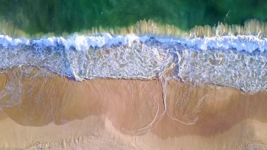 Narrow beach line, waves and ocean. Aerial view.