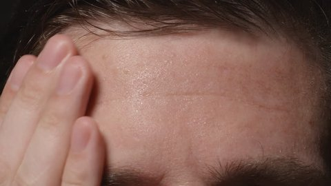 Man wipes his sweating forehead - Close up