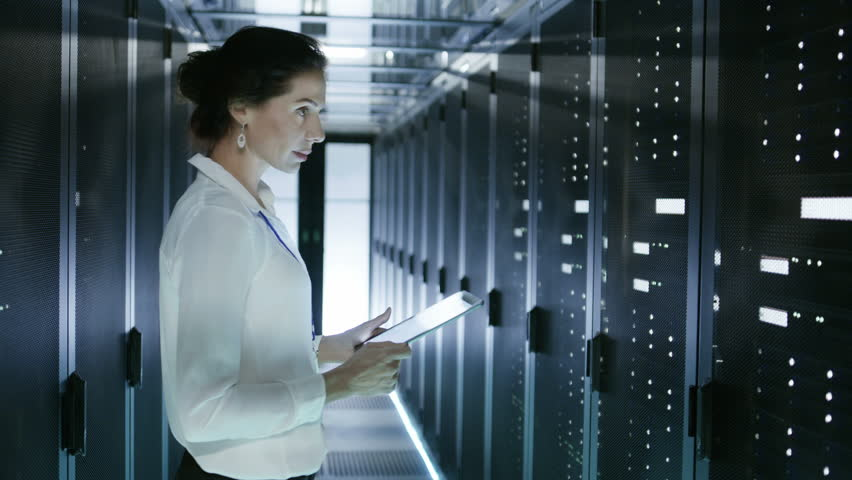 Female Server Technician Walking in Data Center Corridor with Rows of Rack Servers. She's Running Diagnostics on Her Tablet Computer. Shot on RED EPIC-W 8K Helium Cinema Camera. | Shutterstock HD Video #25116896