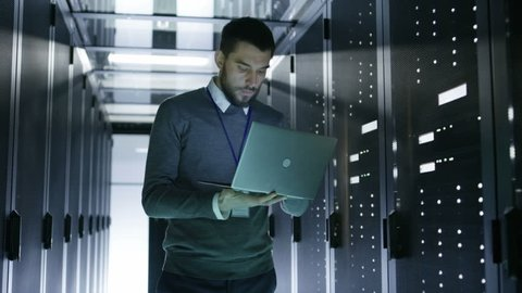 IT Technician Walks and Works on a Laptop in Big Data Center full of Rack Servers. He Runs Diagnostics and Maintenance Stets up System. Shot on RED EPIC-W 8K Helium Cinema Camera.