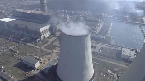 Flying over the large pipe plant for the production of thermal energy Aerial. Breathtaking Aerial Flyover Of Factory, Smoke Stack, Industrial Energy plant.