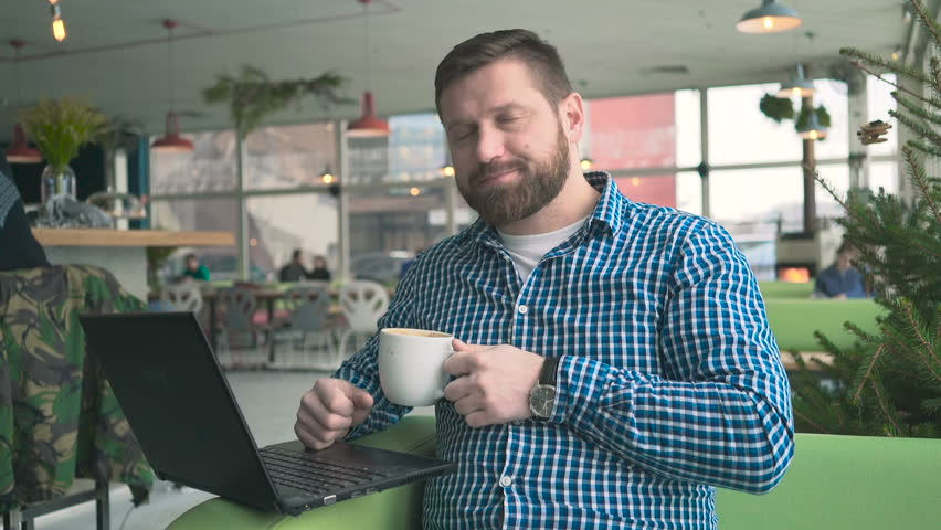 Man browsing laptop, drink coffee, look at camera, cafe, portrait, steadycam  | Shutterstock HD Video #25119476