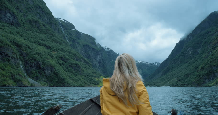 Brave Woman taking photograph in stormy weather on Fjord Norway with smartphone photographing scenic landscape nature background view enjoying vacation travel adventure