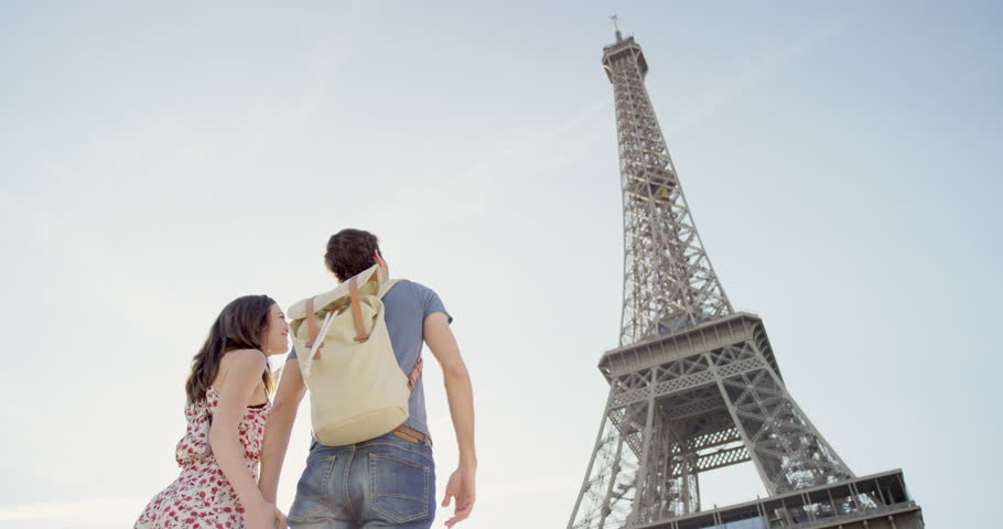 Happy tourist couple looking up at Eiffel Tower sightseeing enjoying European summer holiday travel vacation adventure | Shutterstock HD Video #25127396