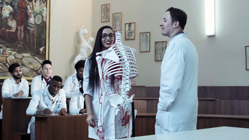 Video clip of young woman student weared eyeglasses in anatomy class with teacher and skeleton dummy. 4K middle shot | Shutterstock HD Video #25129628