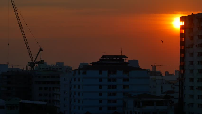 Crane building with backdrop is sunset; There are small birds flying around; Fair in the video. | Shutterstock HD Video #25140356