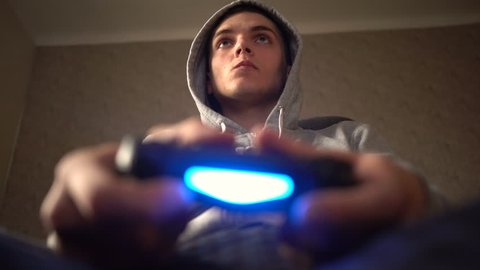 Young Man Absorbed In Online Video Game. Controller, console, gamepad