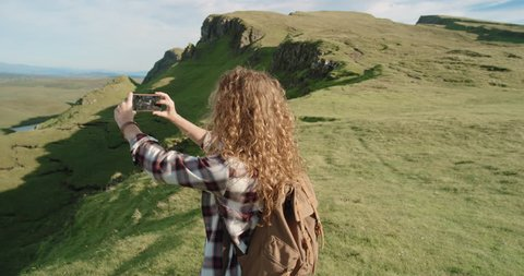 Hiker Woman taking photo smartphone photographing scenic landscape nature background view Hipster girl enjoying vacation travel adventure. Quiraing Walk on the Isle of Skye in Scotland