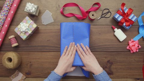 Aerial lockdown footage of woman wrapping gift box with blue paper. Personal perspective of female preparing presents for occasion. Overhead flat lay of art and craft equipment on wooden table.