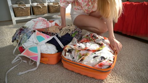 A young woman is trying to close the chock-full suitcase.