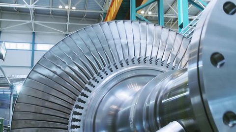Power steam turbine rotates at a heavy industry plant producing power. Steam turbines and power steam turbine blades