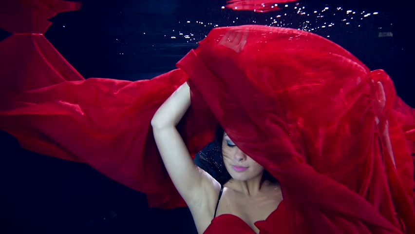 Ecstasy in motion under water. Sexy dance young beautiful girl in zero gravity. Red long dress