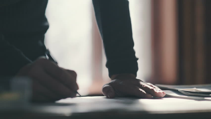 Close-up: the man bends over the desk and makes notes with a pen, leaning on the table. Close-up: a writing pen. The man's hand holds the pen and guides the line along the paper. | Shutterstock HD Video #25203713