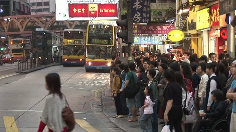 Hong Kong, China - CIRCA April, 2007: A large crowd of people wait and then cross an intersection going both ways in a busy shopping area