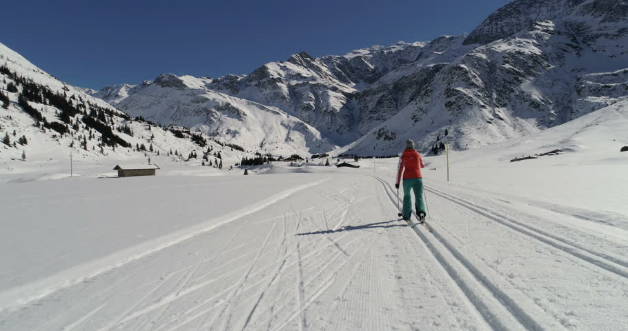 Sporty woman cross country skiing on groomed-trail. Classic skiing