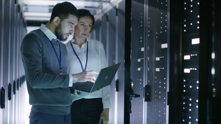 Male and Female Server Engineers Work on a Laptop in Data Center. He Opens Rack Server Cabinet. Shot on RED EPIC-W 8K Helium Cinema Camera.