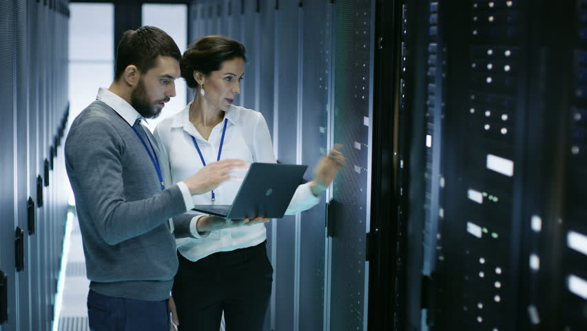 Male IT Specialist Holds Laptop and Discusses Work with Female Server Technician. They're Standing in Data Center, Rack Server Cabinet is Open. Shot on RED EPIC-W 8K Helium Cinema Camera. | Shutterstock HD Video #25243136