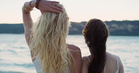 Two woman arm in arm watching sunset over lake best friends looking to the future hair blowing in wind wearing denim summer shorts on road trip adventure