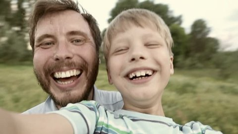 Portrait of happy caucasian family spinning around while taking selfie in countryside. Laughing daddy and son posing for camera in sunset time on summer day. Slow motion wide angle hd video footage.