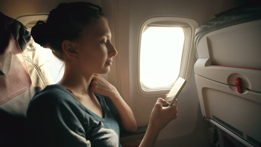 Tourist woman sitting near airplane window at sunset and using mobile phone during flight | Shutterstock HD Video #25275656