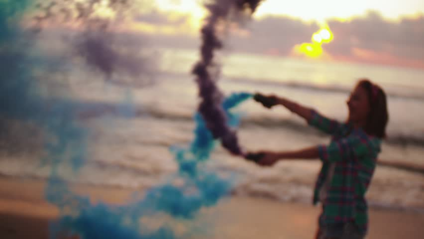 Young teenage girl playing with blue and purple smoke grenades on seaside at sunset