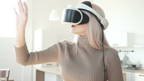 Future is right now. Young woman using 3D virtual reality headset. Virtual reality game. Girl with pleasure uses head-mounted display. Beautiful young woman playing game in virtual reality glasses.