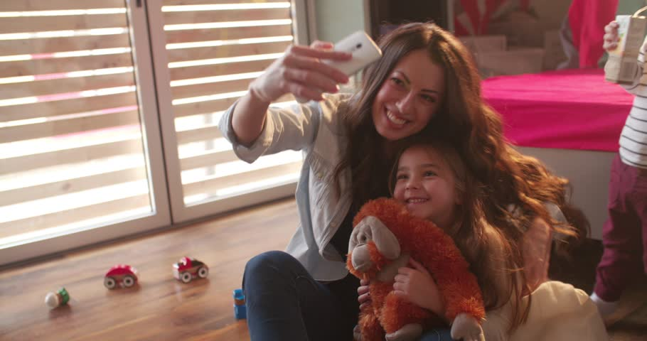 Young aunt teasing and tickling her niece while taking a selfie with her | Shutterstock HD Video #25287086